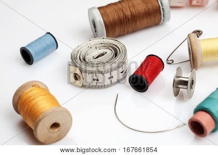 Spools Of Thread, Needles And Other Sewing Stuff On A White Background, Close-up Shot.