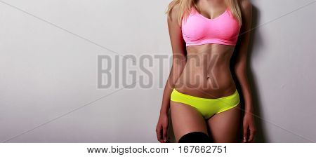 Beautiful sporty female body in pink and green bikini isolated on gray background