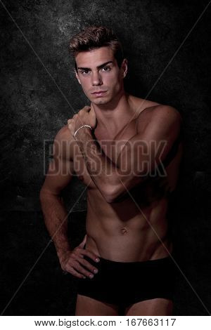 Italian model muscular man. Underwear portrait. A young Italian boy shirtless posing on a grunge black and white background. Muscular and athletic. Well-defined muscles.