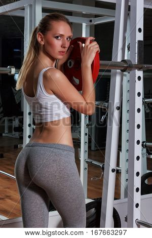 Blonde girl chooses for himself the appropriate weight of the barbell in the gym