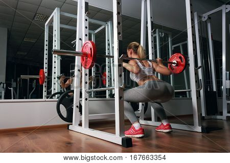 Young sexy blonde european girl in the gym doing squat with barbell in front of the mirror. She is dressed in sports clothes white top, gray leggings, orange sneakers
