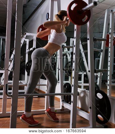 Young sexy girl lifts a heavy barbell in the fitness center. She is wearing a gray leggings, which emphasize excellent figure