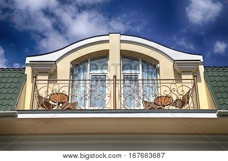 Arch window and balcony in attic floor of luxury mansion on summer blue sky background.