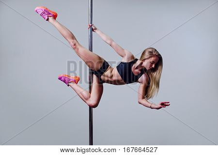 Young sexy pole dance woman on grey background