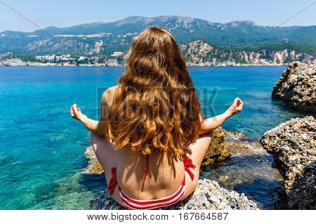 Young woman sitting in lotus position on the beach