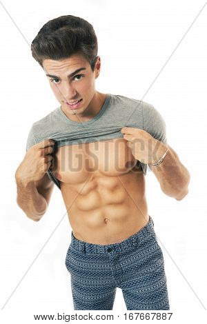 Man athletic with gray t-shirt showing abs. A handsome boy is showing his abs by lifting his shirt. He wears fancy pants and grey t-shirt. He has a physical sculptural and athletic. Hair fashion.