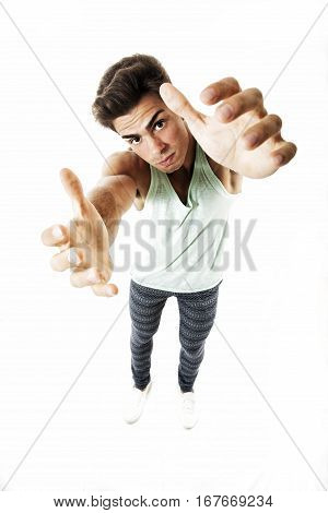Man from above trying taking something with two hands on white. A young man seen from above stretches out his arms to catch and grab something with two hands. In studio on white background.