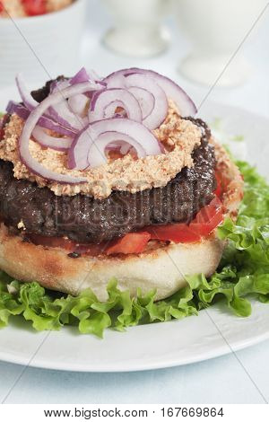 Pljeskavica, serbian ground beef burger with onion and urnebes salad