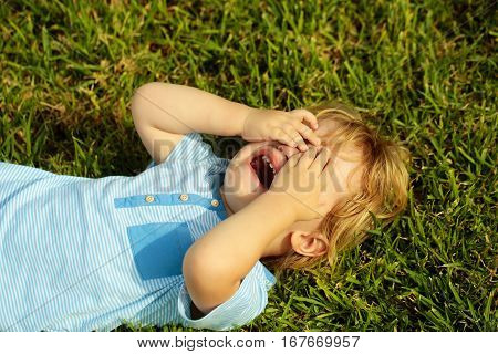 Crying cute baby boy with blond hair in blue tshirt hides face with hands lying on green grass outdoors on sunny summer day on natural background