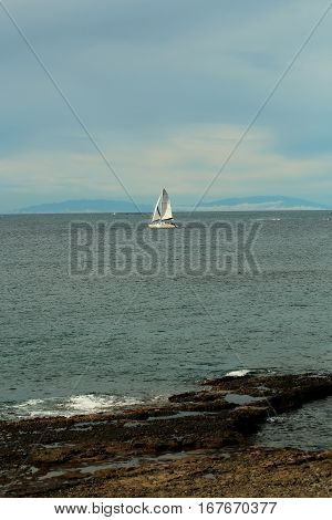 Beautiful sailing ship or yacht boat with white sails in calm blue sea water floats inshore outdoors on sunny summer day on sky background