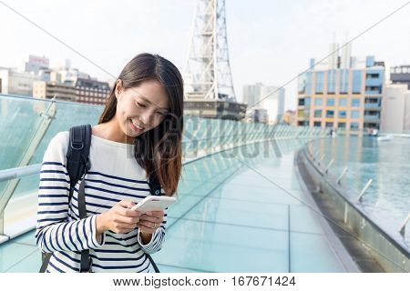 Asian woman sending sms on mobile phone in Nagoya city
