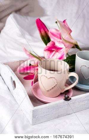 tray with cup of hot tea and flowers in the bed, lazy morning, valentines day