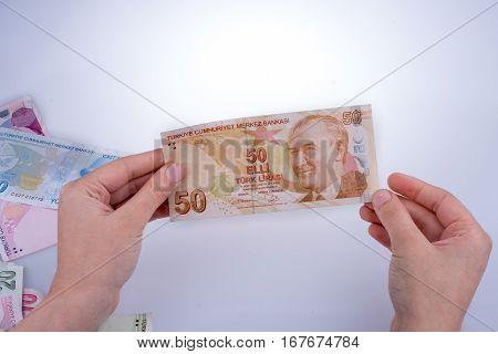 Hand holding Turksh Lira banknote on white background