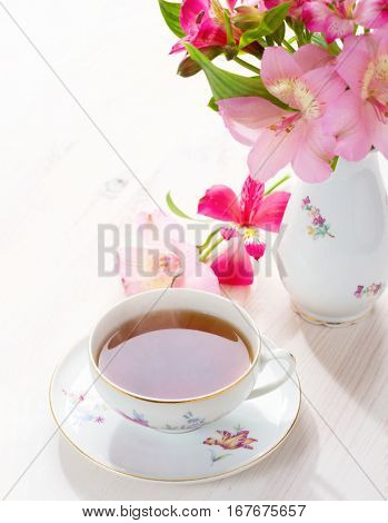Cup of tea and flowers (Alstroemeria).