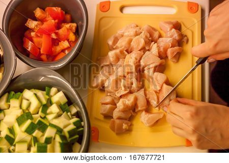 female hands cooking ragu of tomatoes zucchini and chicken
