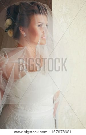 A Brunette Bride Looks Far Away Standing Behind A Window