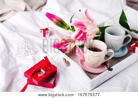 present box, tray with cup of hot tea and flowers in the bed, lazy morning, valentines day