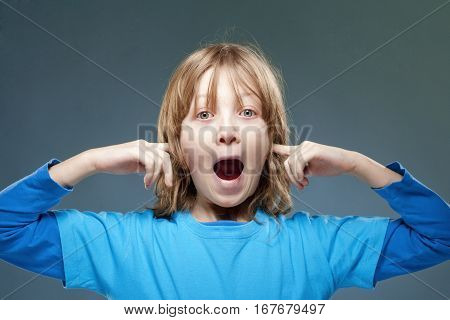 Boy Putting his Index Fingers in his Ears not to Hear