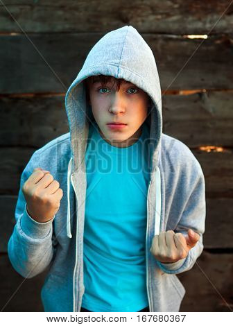 Angry Teenager in Boxer Pose on the Wooden Background