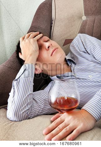 Tired Young Man sleep with Glass of Brandy on the Sofa at the Home