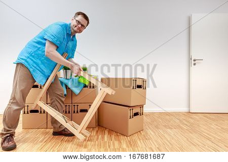 Man fighting with wooden bock. He stands beside moving boxes.