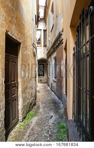 Narrow passage between buildings. Old walls with cracked paint. Explore an old town.