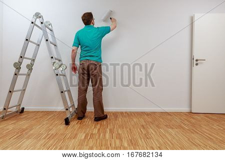 Man is painting a wall white. He looks exhausted.