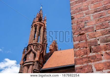 Red brick wall. Church tower on sky backdrop. Visit the God's temple.