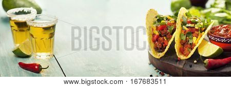 Mexican nachos chips and tacos with meat, beans and salsa on rustic background