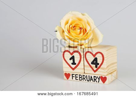 Valentine's day composition with wooden calendar and yellow rose. Handwritten February, one and four inside red hearts. Bright background. Copy space.