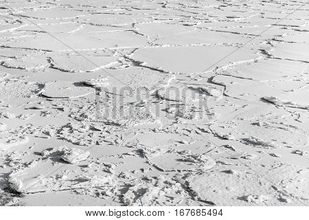 Frozen ice beneath white snow at sunny day