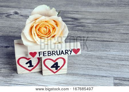 Valentine's day composition with wooden calendar and yellow rose. Handwritten February, one and four inside red hearts. Gray wooden background. Copy space.
