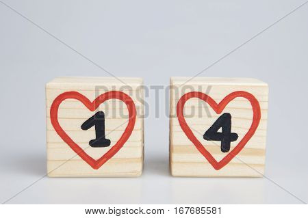 Valentine's day. Wooden cubes with handwritten number one and four inside red hearts. Copy space