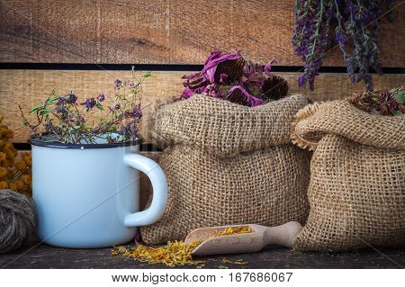 Hessian Bags Of Dry Healthy Flowers, Bunches And Enameled Cup Of Medicinal Herbs, On Wooden Board. H