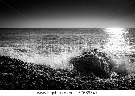 Sea waves crashing on a rock in the beach. Black and white photography.