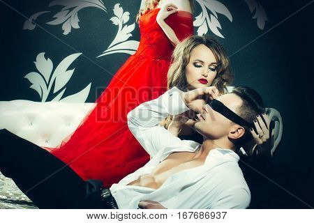 Sexy man in unbottoned shirt with tied eyes. Pretty girl in gorgeous dress tied the man's eyes with black stripe