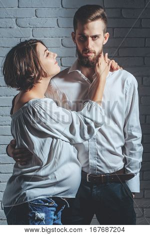 family parent couple of pretty happy sexy woman or cute pregnant girl with round belly or abdomen and handsome bearded man hipster in white shirt on brick wall background at mothers day