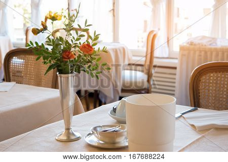 Flowers on dining table. Food establishment interior. Tasty food and quality service.