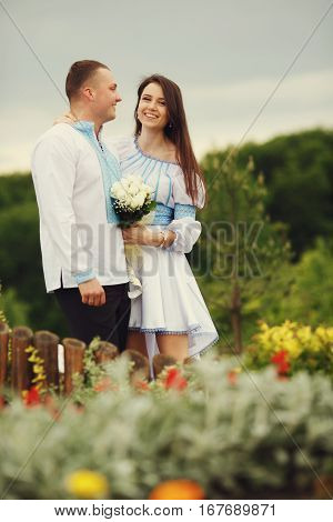 A View From Flowers On A Wedding Couple Dressed In Blue And White Embroidered Costumes