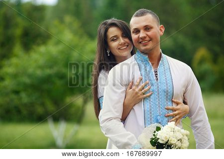 Pretty Brunette Bride Hugs From Behind A Groom In Blue Embroidered Shirt