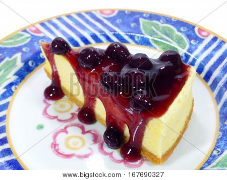 Mouthwatering baked cheesecake with blueberry sauce served on vibrant colored pattern plate