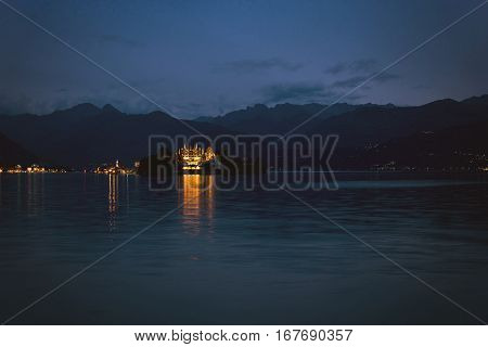 Water and mountains at night. Town lights on coast. Isola Bella from distance.