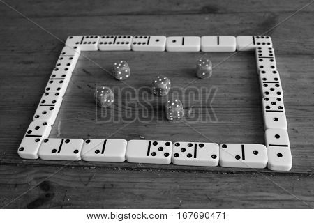 Classic poker dices close up on wooden brown background with domino game frame in black and white style