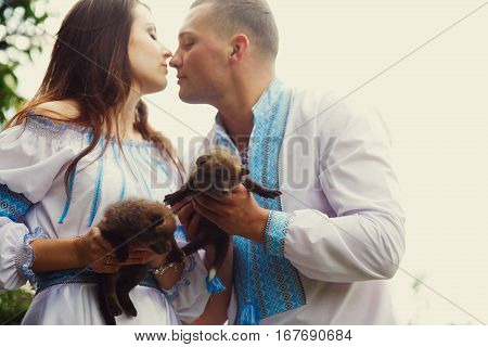 A Wedding Couple Dressed In Ukrainian Ethnic Style Touches With Their Noses Tenderly Holding Little