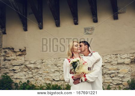 Groom In An Embroidered Shirt Hugs Bride From Behind And Kisses Her