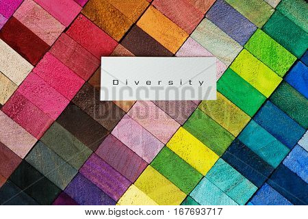 """Cover for creative works. Spectrum of multi colored wooden blocks with white paper area with """" Diversity """" text . Background or cover for something creative or diverse."""