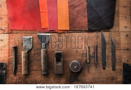 Leather craft. Well used leather craftman's tools and pieces of beautifully colored or tanned leather on grungy work desk .