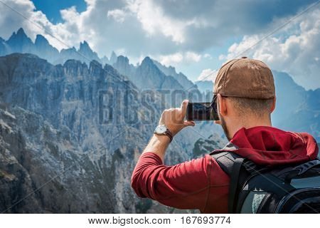 Hiking Tourist Taking Photos Using His Hi-End Smartphone Device. Travel Concept. Mountain Hiker.