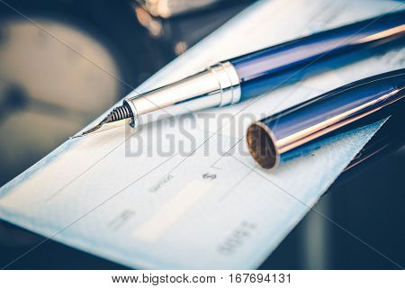 Issuing Payment by Check by Using Elegant Fountain Pen. Executive Desk Closeup.