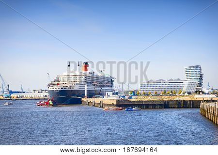 HAMBURG GERMANY - SEPTEMBER 28 2016: Queen Mary 2 cruise ship in the Port of Hamburg and the Elbe river on September 28 2016